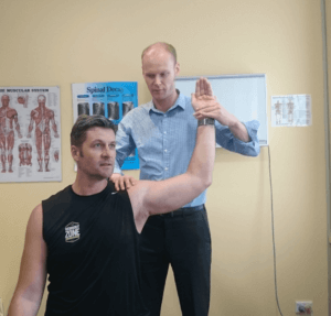 sports chiropractor assessing a patients shoulder