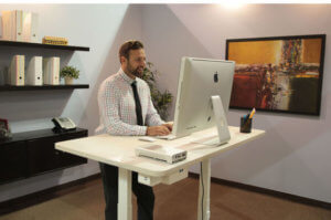 man working in office at a standing desk