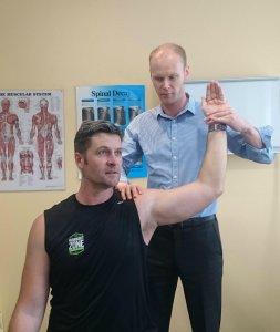 chiropractor assessing a patients shoulder