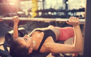 a girl doing a benchpress at the gym