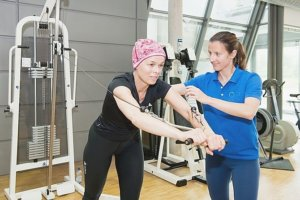a cancer patient exercising with a physiotherapist