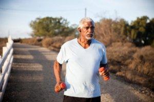 older man running with hand weights